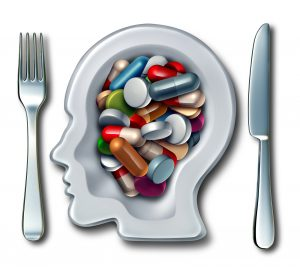 Brain drugs and neuroscience medicine concept as a dinner plate with knife and fork shaped as a human head with medication as pills and capsules as a smart drug mental health symbol for research in new neurology therapy.