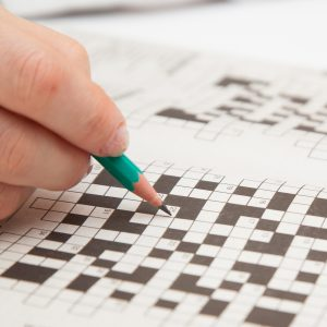 Crossword puzzle close-up.Hand doing crossword.